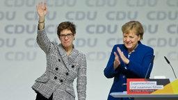 Annegret Kramp-Karrenbauer (l.) winkt nach ihrer Wahl zur CDU-Vorsitzenden in Hamburg. Ihre Vorgängerin Angela Merkel steht daneben und klatscht. © picture alliance / AA Foto: Abdulhamid Hosbas