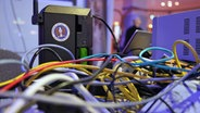 Bunte Kabel vor einem schwarzen Gerät mit einem Sticker der NSA. © NDR Foto: Carolin Fromm