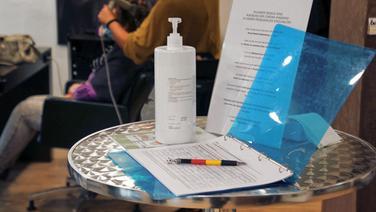 Eine Liste mit Kundendaten liegt in einem Friseursalon auf dem Tisch. | imago