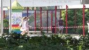 Schüler gehen am Hamburger Lise-Meitner-Gymnasium hinter Absperrband entlang. © TeleNewsNetwortk