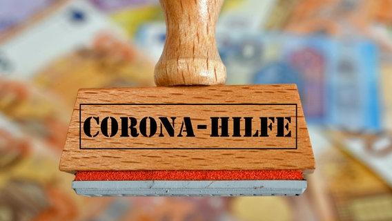 Ein Stempel mit der Aufschrift Corona-Hilfe. © picture alliance / Eibner-Pressefoto Foto: Weber/Eibner-Pressefoto