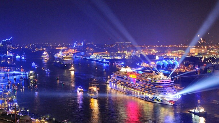 Kreuzfahrtschiffe bei den Cruise Days im blau illuminierten Hamburger Hafen.