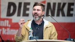 Der Spitzenkandidat der Linken in Hamburg, Fabio De Masi, spricht auf einer Bühne in der Hansestadt. © dpa-Bildfunk Foto: Daniel Reinhardt