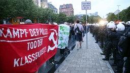 Polizisten und Demonstranten mit Transparenten stehen sich am 29.06.2017 bei einer Demonstration von G20-Gipfel-Gegnern auf der Reeperbahn in Hamburg gegenüber. © dpa - Bildfunk Fotograf: Bodo Marks