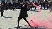 Ein Demonstrant wirft eine Rauchpatrone in Richtung der Polizeikräfte bei einer aufgelösten Demonstration in Hamburg. © picture-alliance/dpa Foto: Christian Charisius