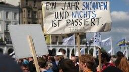 """Demonstranten halten auf dem Hamburger Rathausmarkt Schilder hoch, auf einem ist zu lesen: """"Ein Jahr Snowden und nichts ist passiert"""". © dpa-Bildfunk Fotograf: Axel Heimken"""