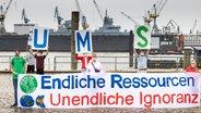"""Aktivisten von """"Fridays for Future"""" und BUND demonstrieren auf dem Fischmarkt in Hamburg mit einem Banner mit der Aufschrift """"Endliche Ressourcen, Unendliche Ignoranz"""", um auf den globalen Erdüberlastungstag 2020 aufmerksam zu machen. © picture alliance / dpa Foto: Ulrich Perrey"""