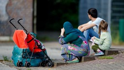 Flüchtlinge sitzen in Hamburg auf dem Hof einer ehemaligen Schule. © dpa-Bildfunk Fotograf: Daniel Bockwoldt