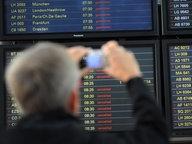 Ein Reisender macht ein Foto von der Anzeigetafel mit gestrichenen Abflüge am Flughafen in Hamburg © dpa Fotograf: Christian Charisius