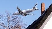 Ein Flugzeug fliegt in Hamburg dicht über Häuser hinweg. © picture alliance / dpa Fotograf: Daniel Bockwoldt