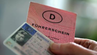 Zwei Führerscheine verschiedener Generationen hält eine Frau in der Hand. © picture alliance/dpa Foto: Oliver Berg