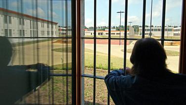 Ein Mann schaut durch ein vergittertes Fenster. | dpa - Bildfunk