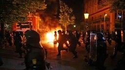 Polizisten rennen über das Schulterblatt im Hamburger Schanzenviertel. Im Hintergrund brennt eine Barrikade. © dpa Fotograf: Christian Charisius