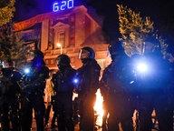 Polizisten stehen im Schanzenviertel vor der Roten Flora - einem Zentrum linker Aktivisten. Im Hintergrund brennen Barrikaden. © dpa Foto: Axel Heimken