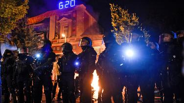 Polizisten stehen im Schanzenviertel vor der Roten Flora - einem Zentrum linker Aktivisten. Im Hintergrund brennen Barrikaden. © dpa Fotograf: Axel Heimken