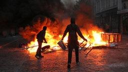 Zwei Randalierer stehen im Schanzenviertel vor einer brennenden Barrikade. © dpa