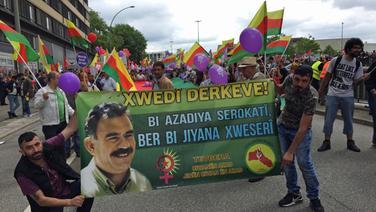 Kurden aus ganz Deutschland kommen zum Demonstrieren in Hamburg zusammen und halten ein Banner hoch. © NDR Fotograf: Susanne Röhse