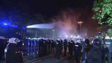 Ein Wasserwerfer in Aktion gegen einige Demonstranten im Vorfeld des G20-Gipfels, dazwischen eine Reihe Polizisten. © TV Elbnews / Andre Hellwig Fotograf: Andre Hellwig