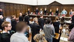 Im Zusammenhang mit Ausschreitungen während des G20-Gipfels stehen die Angeklagte mit ihren Anwälten im Landgericht im Saal. Bei der strafrechtlichen Aufarbeitung der Ausschreitungen während des G20-Gipfel geht es erstmals um die Ereignisse an der Elbchaussee. © picture alliance / dpa Foto: Daniel Bockwoldt