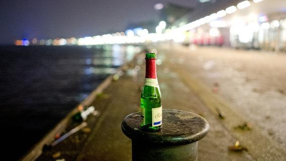Leere Sektflasche steht auf einem Poller an den Landungsbrücken in Hamburg. © dpa - Bildfunk Fotograf: Daniel Bockwoldt