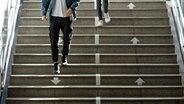 Neu angebrachte Pfeile auf einer Treppe weisen den Fahrgästen im U-Bahnhof Wandsbek Markt die optimale Laufrichtung. © picture alliance/dpa Foto: Daniel Reinhardt