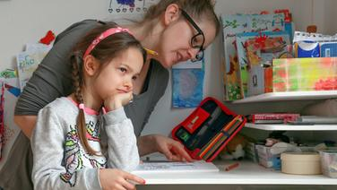 Eine Frau und ein Mädchen sitzen an einem Schreibtisch. © picture alliance/dpa Themendienst Foto: Mascha Brichta