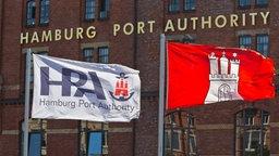 Die Fahnen der Hamburg Port Authority und der Freien und Hansestadt Hamburg wehen in der Hamburger Speicherstadt. © picture alliance / dpa Foto: Markus Scholz