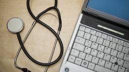 Ein Stethoskop liegt neben einem Laptop. © dpa/picture alliance Foto: Patrick Peul
