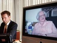 Roger Kusch neben einem TV-Bildschirm, auf dem die verstorbene Frau aus Würzburg zu sehen ist. © dpa Fotograf: Marcus Brandt