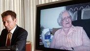 Roger Kusch neben einem TV-Bildschirm, auf dem die verstorbene Frau aus Würzburg zu sehen ist. © dpa Foto: Marcus Brandt