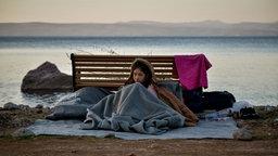 Ein Mädchen sitzt unter Decken des Flüchtlingshilfswerk UNHCR auf der griechischen Insel Lesbos vor einer Bank auf dem Boden. © picture alliance / ZUMAPRESS.com Foto: Eurokinissi