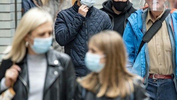 Les passants avec protection buccale et nasale traversent une zone piétonne.  © photo alliance / dpa Photo: Axel Heimken