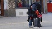 Ein Obdachloser in Hamburg wühlt in einem Blecheimer. © NDR Foto: Marco Peter