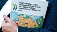 Ein Mann hält einen OECD-Bericht zur Entwicklung der Metropolregion Hamburg in seinem Arm. © picture alliance/Daniel Bockwoldt/dpa Foto: Daniel Bockwoldt