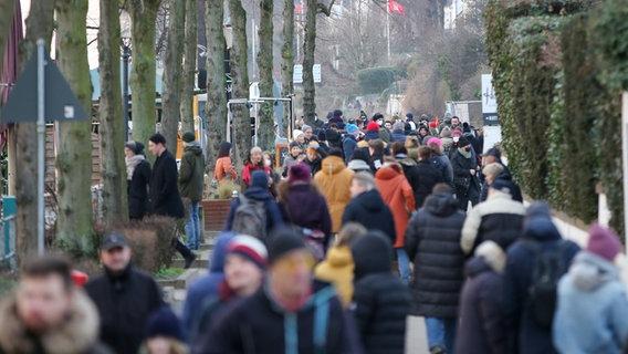Perspektivisch zusammengezogen durch ein Teleobjektiv sind Menschen zu sehen, die bei schönem Wetter auf dem Weg von oder zur Elbe in Hamburg-Övelgönne unterwegs sind. © picture alliance/dpa   Bodo Marks Foto: Bodo Marks