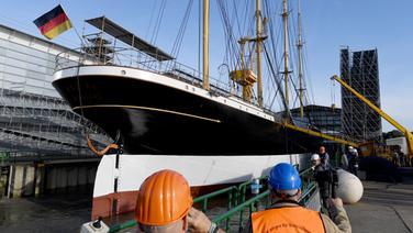 """Das Segelschiff """"Peking"""" liegt vor dem Ausdocken in der Peters Werft, Arbeiter stehen am Pier. © picture alliance / dpa Foto: Carsten Rehder"""