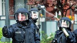 Polizisten setzen während einer Demo gegen einen Nazi-Aufmarsch in Hamburg Pfefferspray ein. © dpa / Picture Alliance Fotograf: Christian Charisius