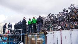 Polizisten stehen zwischen unzähligen Fahrrädern. © dpa - Bildfunk Fotograf: Daniel Bockwoldt