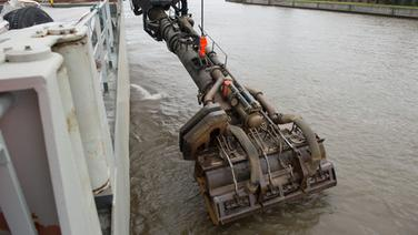 """Der Saugkopf des Baggerschiffes """"Bartolomeu Dias"""" wird in Hamburg in die Elbe gesenkt. Das Spezialschiff baggert Schlick aus der Elbe in seinen Laderaum und verklappt diesen anschließend in der Nordsee. © dpa Bildfunk Foto: Daniel Reinhardt"""