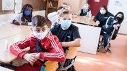 Schüler einer Stadtteilschule sitzen zu Beginn des Unterrichts mit Mund-Nasen-Bedeckungen im Klassenraum. © picture alliance/dpa Foto: Daniel Bockwoldt