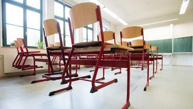 Stühle stehen auf Tischen in einem leeren Klassenzimmer einer Schule. | picture aliance / dpa-Zentralbild