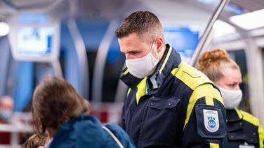 Mitarbeiter der Hamburger Hochbahn-Wache kontrollieren die Einhaltung der Maskenpflicht in einer U-Bahn.   picture alliance/dpa