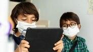 Zwei Schüler mit Mundschutz schauen auf ein Tablet. © imago images Foto: imago images / Westend61