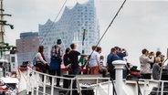 """Menschen sind auf dem Heck des Feuerschiffs """"Borkumriff"""" vor der Elbphilharmonie zu sehen. © picture alliance/Markus Scholz Foto: Markus Scholz"""