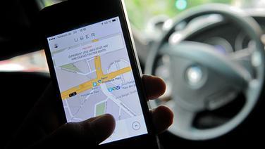 Auf einem Smartphone ist die App des Fahrdienstvermittlers Uber zu sehen © dpa Foto: Britta Pedersen