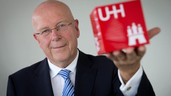 Dieter Linzen, president van de universiteit van Hamburg, toont een kubus met het logo van de universiteit erop.  © foto alliantie / Christian Charicius / DPA