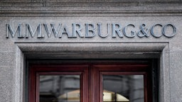 Das Logo des Bankhauses M.M.Warburg & CO ist in großen Lettern über dem Haupteingang in Hamburg befestigt. © dpa