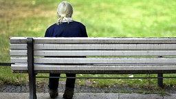 Eine alte Frau sitzt auf einer Parkbank. © picture-alliance/ ZB Foto: Arno Burgi