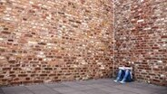 Ein junges Mädchen sitzt mit gesenktem Kopf vor einer hohen Mauer. © photocase.de Foto: Mr. Nico