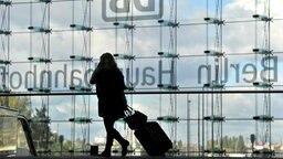 Eine Reisende zieht im Hauptbahnhof in Berlin ihren Koffer hinter sich her. © dpa Foto: Marius Becker